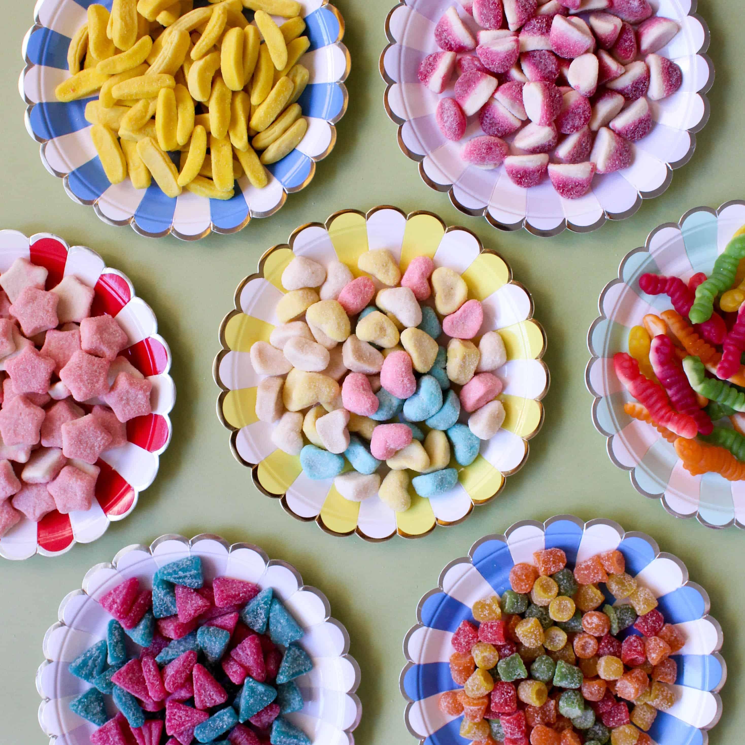 įvairūs spalvoti saldainiai lekštėse